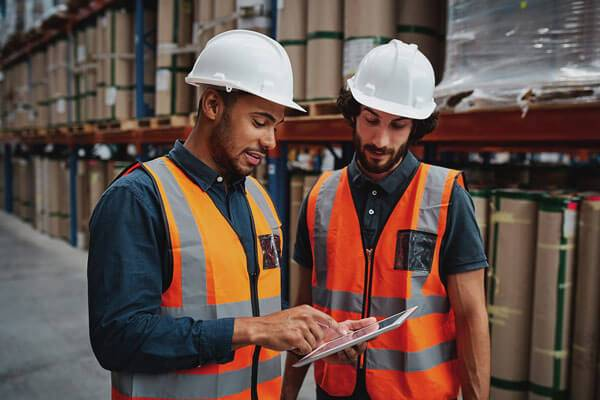 construction professionals working together in warehouse on tablet